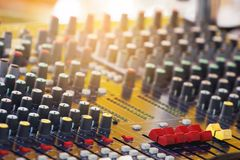 Slide the volume of the mixer in the control room. Volume adjustment knob of audio mixer stock image