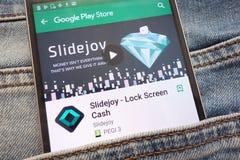 Slidejoy - l'appli d'argent liquide de Lock Screen sur le site Web de Google Play Store montré sur le smartphone caché dans des j photographie stock libre de droits