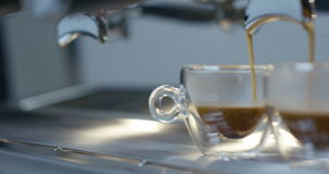 Slider of hot espresso coffee pouring into a two transparent cups from coffee machine in 4k stock video footage