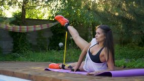 Slider shooting as a girl by the pool training legs, slow motion. A slender brunette lies on a rug for yoga and training stock footage