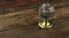 Slider shot. Close-up glass globe for study, standing on a wooden table. stock video