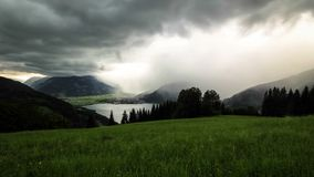 Slider time-lapse of austrian mountains, lake and stormy clouds moving stock footage