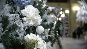 Slider view of white balls and flowers. New Year`s and abstract blurred shopping mall background with Christmas tree stock footage