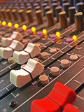 Sliders on audio mixing board. A macro of volume sliders on a soundboard (mixing console) with mute lights and knobs Stock Images