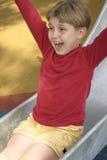 Slides of fun. Child on a metal slide Royalty Free Stock Image