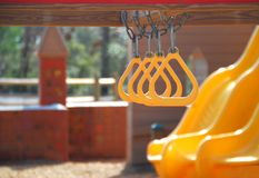 Slides and Rings on Playground. Bright yellow slides and play rings on quiet playground Stock Image