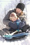 Sliding. Baby and mother sliding on snow during winter Stock Images