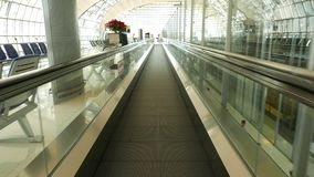 Sliding airport travelator. Walking fast on moving walkway. Subjective view stock video footage