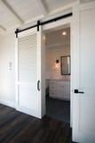 Interior sliding barn doors into bathroom. Sliding barn door entrance into bathroom with mirror, sink, tile floor, and white hardwood cabinets of modern new Royalty Free Stock Photos