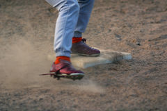 Sliding into Base. Baseball players feet sliding into base amid dust and dirt Royalty Free Stock Image