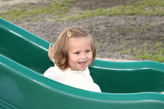 Sliding Board Smile 2. Smiling little girl on a playground sliding board royalty free stock photos