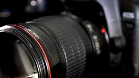 Sliding camera lens with red ring and huge frontal glass element. Sliding camera lens with red ring shot with shallow depth of field, cinematic style. Parallax stock footage