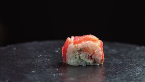 Sliding close up shot of tasty Arigato sushi filled with cheese cream, avocado and cucumber and covered in red roe and