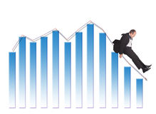 Sliding down. Businessman sliding down upon graph isolated on white royalty free stock photo