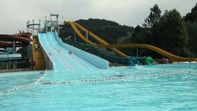 Sliding down the racing pool waterslide stock video