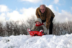Sliding down in the Snow!. Happy little boy (3) on a sleigh ready to slide down a slope in the snow with granddad pushing Stock Photography