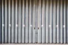 Sliding and folding industrial doors with No Smoking signs. A loading bay for delivery truck on a street of London city stock photography