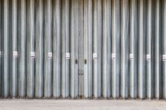 Sliding and folding industrial doors with No Smoking signs. A loading bay for delivery truck on a street of London city royalty free stock image