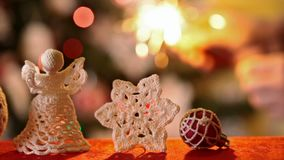 Christmas ornaments with a hand lighting a sparkler in background. Sliding in front of christmas ornaments while a hand lights and holds a sparkler in background stock video