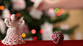 Sliding in front of christmas ornaments. While a hand decorates xmas tree in the background stock footage