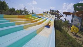 Sliding on the fun water slides in a water park in slow motion stock video