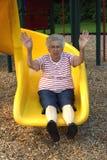 Sliding Grandmother 2. Senior citizen woman on a playground sliding board stock photos