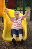 Sliding Grandmother 4. Senior citizen woman with outstretched arms on a playground sliding board stock image