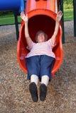 Sliding Grandmother 5. Senior citizen woman on a playground sliding board stock images