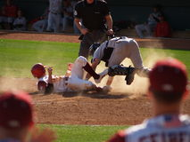 Sliding into Home Plate. A baseball runner slides into home plate knocking dust and the catcher into the air Stock Photos