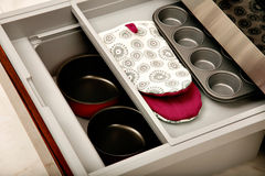 Kitchen drawer with compartments. A sliding kitchen drawer containing saucepans, oven mitts and a muffin tin Stock Photo