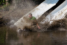 Sliding into mud. An active person slides into a muddy pool, during the July 2014 mudathlon in northwest Indiana Royalty Free Stock Photo