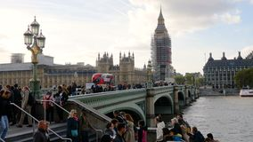 Sliding shot of Big Ben and houses of Parliament during conservation refurbishment, people and traffic on Westeminster Bridge. Sliding shot from left to right of stock video