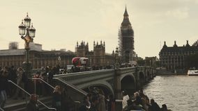 Sliding shot of Big Ben and houses of Parliament during conservation refurbishment, people and traffic on Westminster Bridge. Sliding shot from left to right of stock video footage