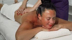 Beautiful masseuse smiling to the camera while working at spa center. Sliding shot of a mature women enjoying soothing back massage at the hands of a stock images