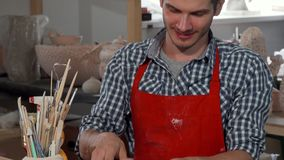 Handsome cheerful male potter enjoying working at his studio stock footage