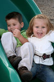 Sliding Siblings 2. Smiling young brother and sister sliding on a sliding board royalty free stock photography
