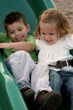 Sliding Siblings 3. Smiling young brother and sister sliding on a sliding board royalty free stock photos