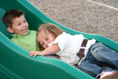 Sliding Siblings 5. Smiling young brother and sister sliding on a sliding board stock photo