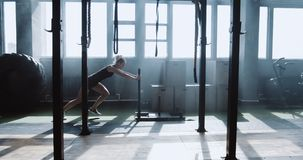 Sliding side view young athletic Caucasian woman exercising with heavy training sled in big atmospheric gym slow motion. Professional female athlete pushing to stock video footage