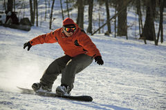 Sliding snowboarder on flank of hill Royalty Free Stock Image