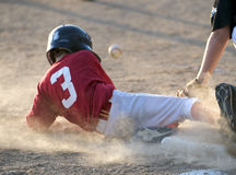 Sliding Into Third. Young boy, playing little league baseball, sliding into third base with dust flying and ball frozen in frame Stock Images