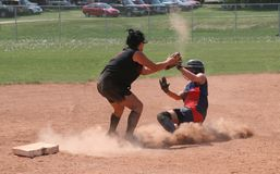 Sliding to Third. A runner sliding into home plate in a fastball game Stock Image