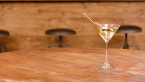 Sliding towards a glass of martini on an empty wooden table. Dry martiny with olives as a garnish stock video footage