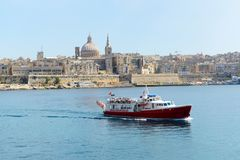The motor boat for tourists cruises and view on Valletta. SLIEMA, MALTA - APRIL 22: The motor boat for tourists cruises and view on Valletta on April 22, 2015 in Stock Images