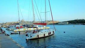 SLIEMA, MALTA - 19 DE JUNHO DE 2018: A linha de iate da vela, amarrada no porto do norte com uma vista em Valletta e em Manoel Is video estoque