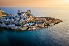 Sliema, Malta - Sunrise at Tigne point with Mediterranean sea. Sliema, Malta - Sunrise at Tigne point with residential buildings Stock Photo