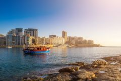 Sliema, Malta - Sunrise with traditional maltese boat and apartments of Tigne point taken from Manoel island. On a hot summer day Royalty Free Stock Photography