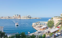 Sliema skyline and ferry. SLIEMA, MALTA - SEPTEMBER 15, 2015: Sliema skyline and ferry en route from Sliema to Valletta ferry terminal on a sunny summer day on Stock Images