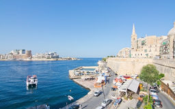 Sliema skyline and ferry. SLIEMA, MALTA - SEPTEMBER 15, 2015: Sliema skyline and ferry en route from Sliema to Valletta ferry terminal on a sunny summer day on Stock Photo
