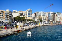 Sliema waterfront buildings, Malta. Tourists walking along the waterfront with a small boat in the foreground, Sliema, Malta, Europe Royalty Free Stock Photo